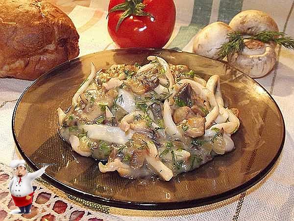 кальмары тушеные с грибами на тарелке