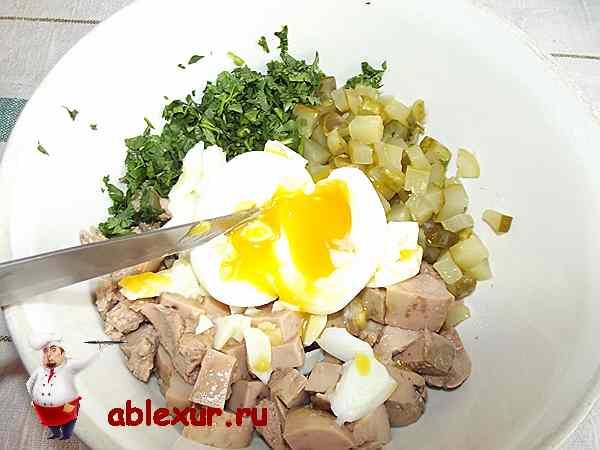 разрезая яйца в салате из печени