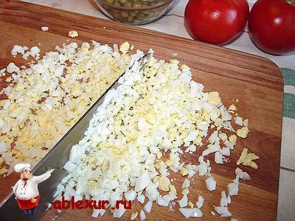покрошенные мелко яйца для салата на разделочной доске
