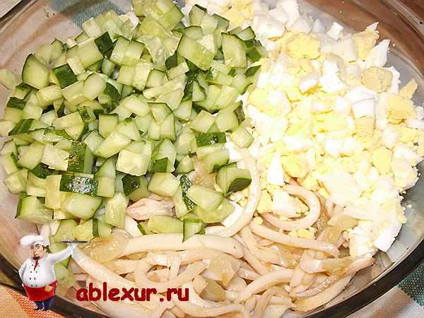 добавленные огурцы и яйца к кальмарам и луку