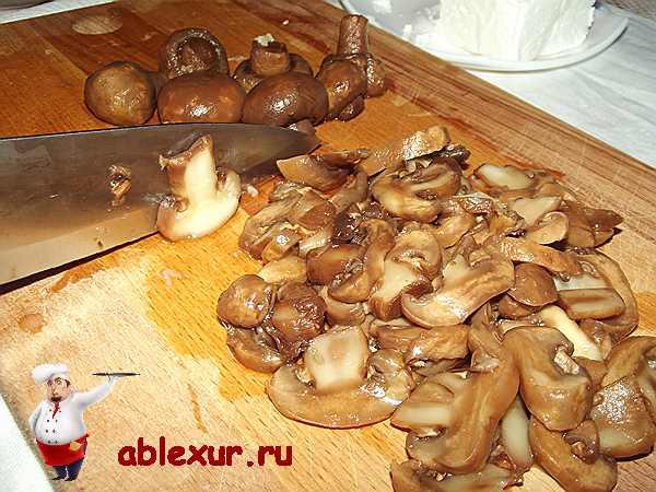 нарезаю грибы пластинками на разделочной доске