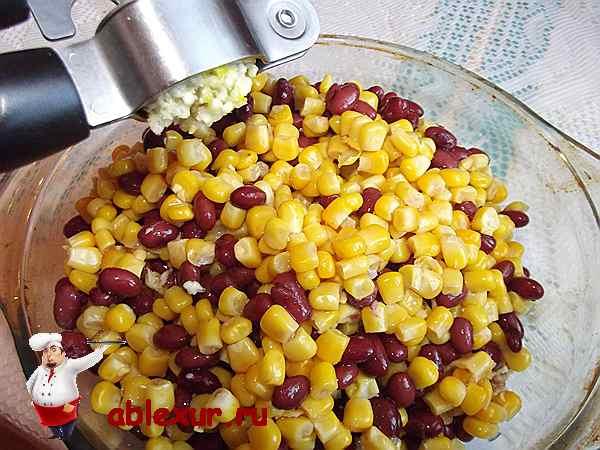 выдавливаю чеснок в салат из кукурузы