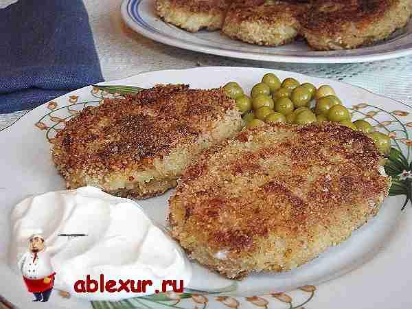 капустные котлеты на тарелке со сметаной и зелёным горошком