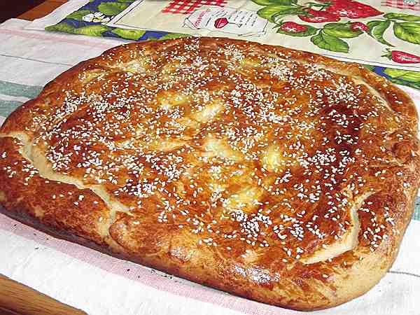 пирог с картошкой и луком лежащий на полотенце