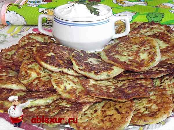 оладьи из кабачков на блюде вместе со сметаной