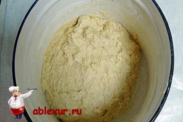 выливаем опару и растопленное сливочное масло в муку и замешиваем тесто для кулича