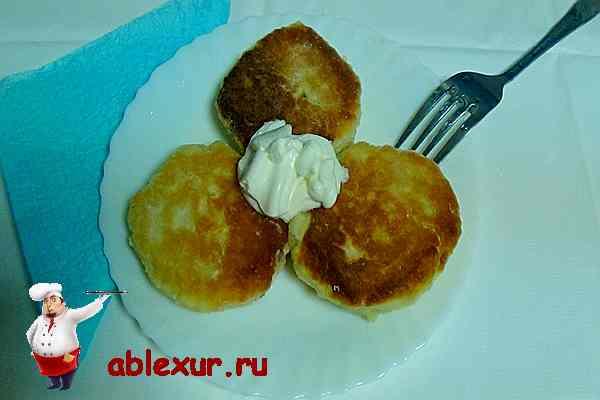 сырники из творога на тарелке со сметаной