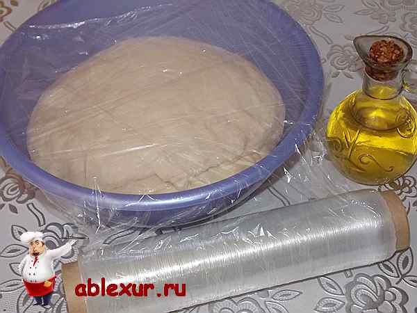 накрытое тесто для пирога с луком пищевой пленкой