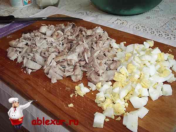 нарезанные кубиками яйца и курица для салата с черносливом