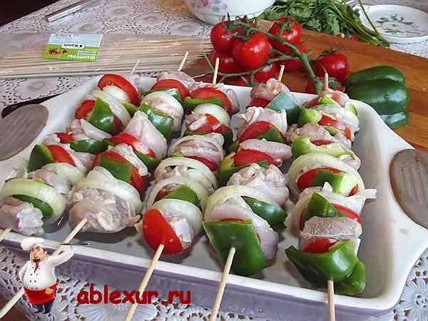 нанизанный на шпажки шашлык и овощи