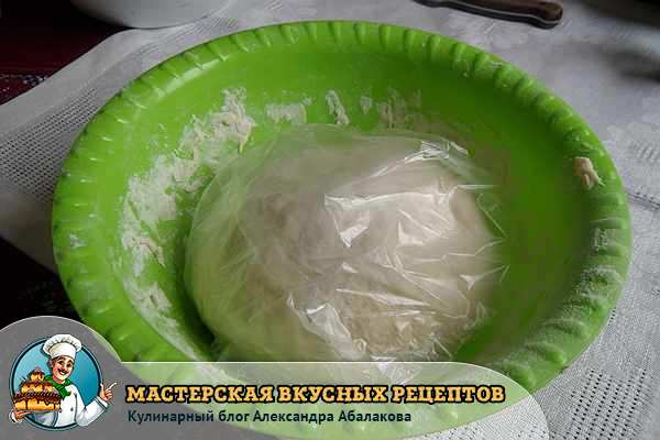 тесто в пищевой пленке лежит в тарелке