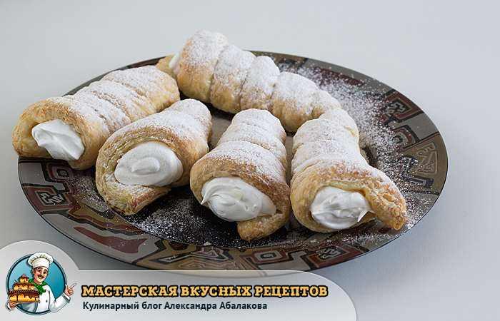 пять трубочек на тарелке присыпаны сахарной пудрой