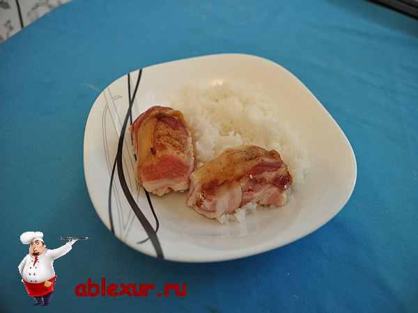 куриные рулетики в беконе с гарниром на тарелке