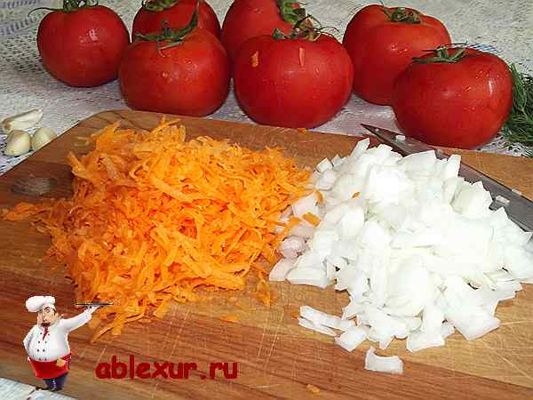 натертая морковь и рубленный репчатый лук на деревянной разделочной доске